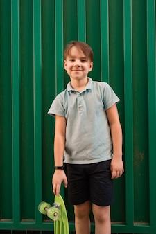 Portret jonge coole lachende jongen in blauwe polo poseren met penny board