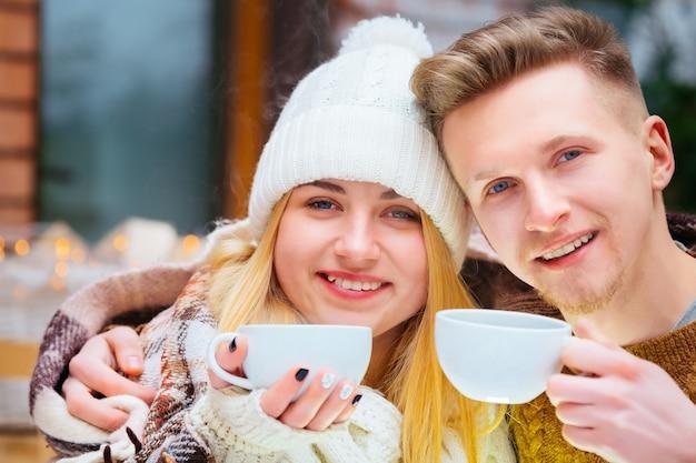 Portret jonge gelukkige romantische paar zitten in café en hand in hand