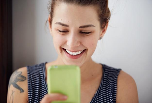 Portret jonge grappige vrouw gelukkig, iets op mobiele telefoon tijdens het sms'en
