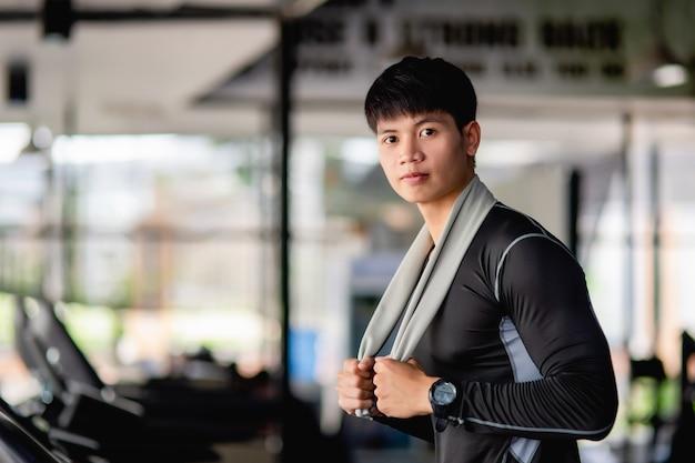 Portret jonge knappe man die loopt om op te warmen voordat hij rent voor een gezonde training op het goede spoor in de moderne sportschool, glimlach en