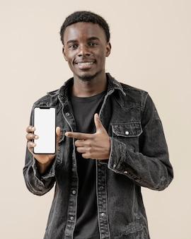 Portret jonge knappe man poseren met mobiel