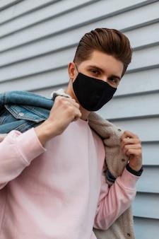 Portret jonge man in denim blauwe stijlvolle jas in roze sweatshirt in zwart beschermend masker op straat. modieuze man loopt in masker op stad. covid-19 virusbeschermingsconcept. nee tegen het coronavirus