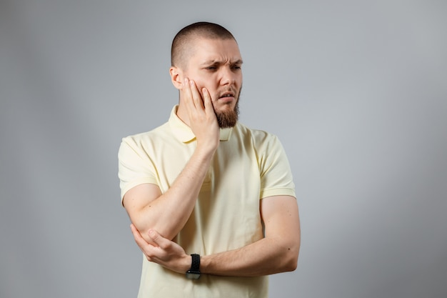 Portret jonge man in gele t-shirt met zijn wang op zoek naar de kant op grijs.