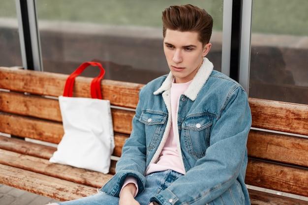 Portret jonge man in stijlvol denim jasje in roze t-shirt in vintage jeans met stof shopper op houten bankje bij halte van openbaar gebouw in de stad. aantrekkelijke man in modieuze kleding rust buiten.