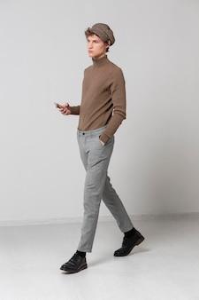 Portret jonge man met hoed met behulp van mobiel