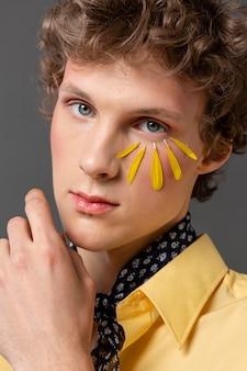 Portret jonge man met make-up poseren Gratis Foto
