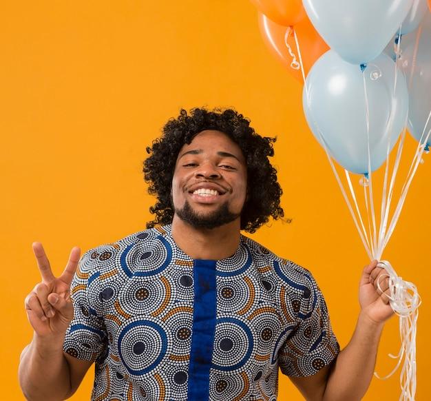 Portret jonge man op feestje met ballonnen