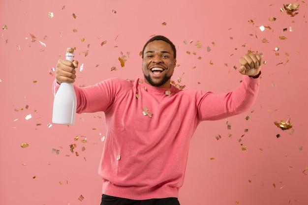 Portret jonge man op feestje met champagne fles