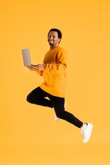 Portret jonge man springen met laptop