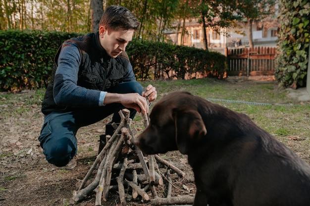 Portret jonge man stapel hout voorbereiden om in brand te steken. hondencamping, natuurlijk levensstijlconcept.
