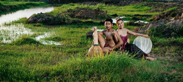 Portret jonge man topless dragen lendenen in landelijke levensstijl zitten in de buurt van mooie vrouw met bamboe visserij val