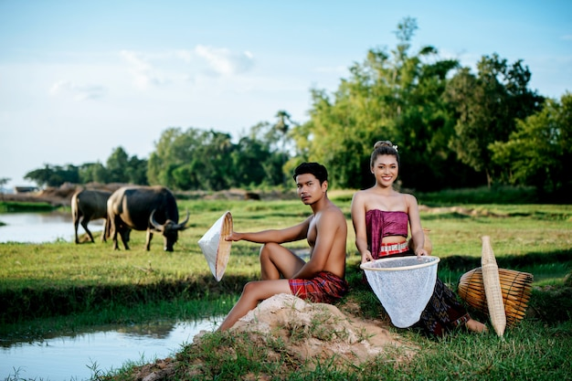 Portret jonge man topless zittend in de buurt van mooie vrouw in mooie kleding in landelijke levensstijl