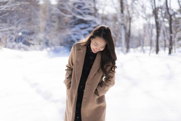 Portret jonge mooie aziatische vrouw glimlach gelukkig reizen en genieten met sneeuw winterseizoen