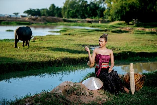 Portret jonge, mooie aziatische vrouw in prachtige thaise traditionele kleding op het rijstveld, ze zit in de buurt van visuitrusting