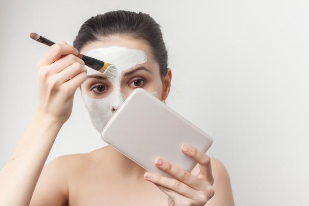 Portret jonge mooie vrouw die een gezichtsmasker met een borstel toepast