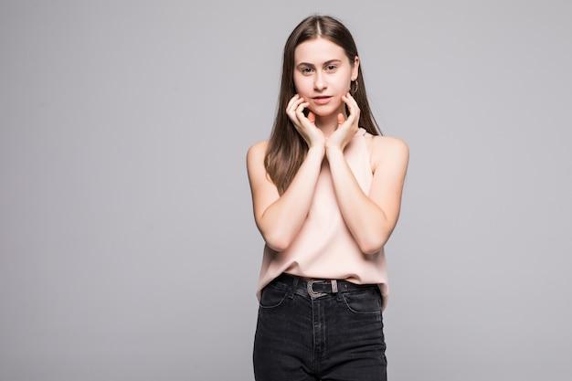 Portret jonge mooie vrouw die over witte muur wordt geïsoleerd