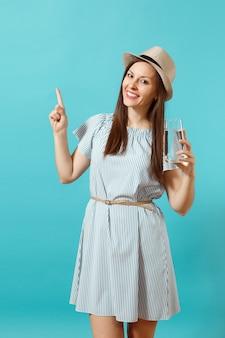 Portret jonge mooie vrouw in blauwe jurk, hoed met glas helder vers zuiver water geïsoleerd op blauwe achtergrond. gezonde levensstijl, mensen oprechte emoties concept. wijzende hand op kopie ruimte.