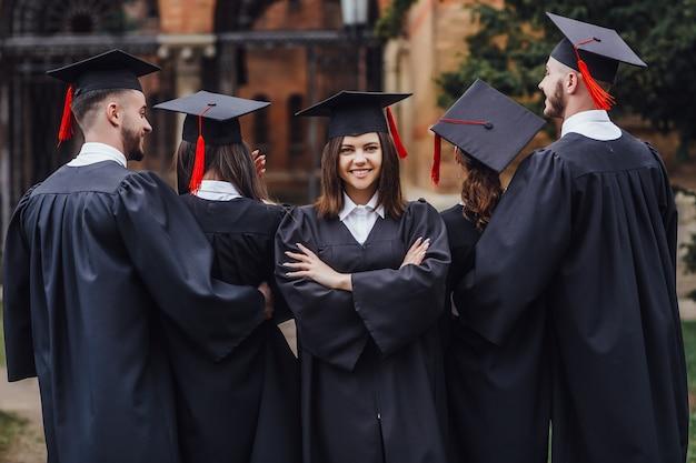 Portret jonge mooie vrouw klaar met onderwijs, ze draagt op zwarte mantel