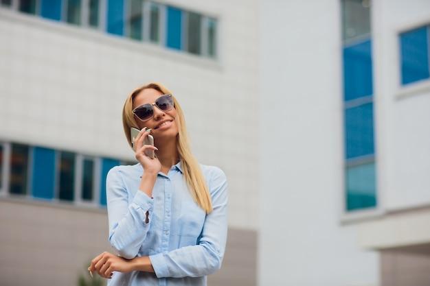Portret jonge onderneemster die op celtelefoon communiceren terwijl het leunen op glasmuur