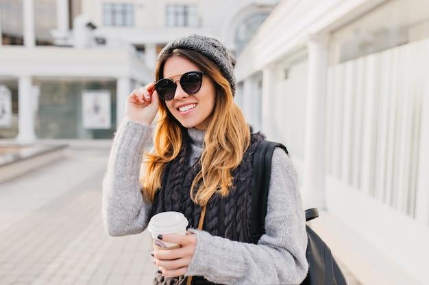 Portret jonge stad modieuze vrouw in moderne zonnebril, warme wollen trui, gebreide muts glimlachend op straat. vrolijke stemming, positieve emoties, wandelen met koffie om mee te nemen.
