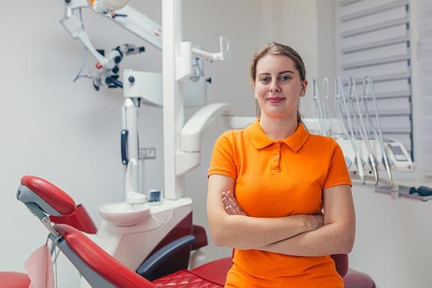Portret jonge vriendelijke vrouwelijke tandarts lacht en kijkt naar de voorkant in een moderne tandartspraktijk
