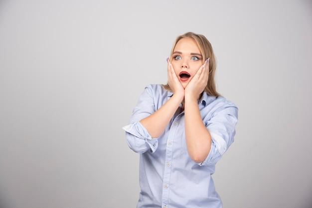 Portret jonge vrouw die opgewonden kijkt met geopende mond en handen omhoog houdt in de buurt van wangen.