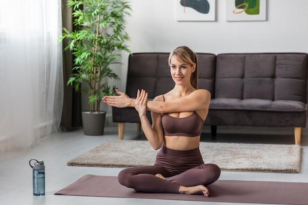 Portret jonge vrouw die zich uitstrekt thuis op de mat
