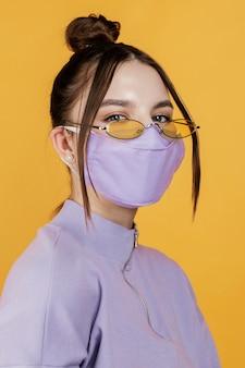 Portret jonge vrouw die zonnebril en masker draagt