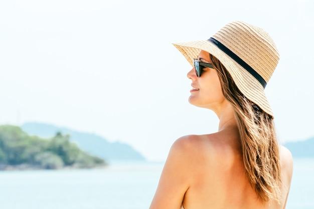 Portret jonge vrouw draagt een strooien hoed op strand
