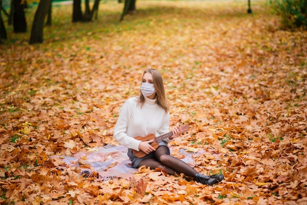 Portret jonge vrouw in beschermend masker ukelele gitaar spelen in herfst park