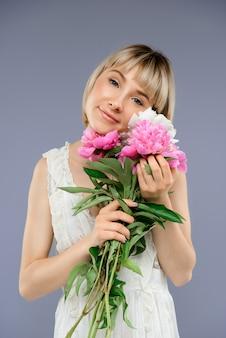 Portret jonge vrouw met boeket bloemen over grijze backgro