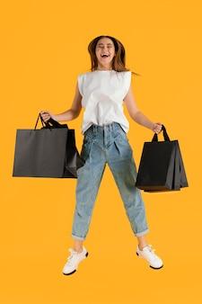 Portret jonge vrouw met boodschappentassen springen