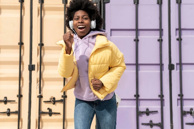Portret jonge vrouw met koptelefoon springen