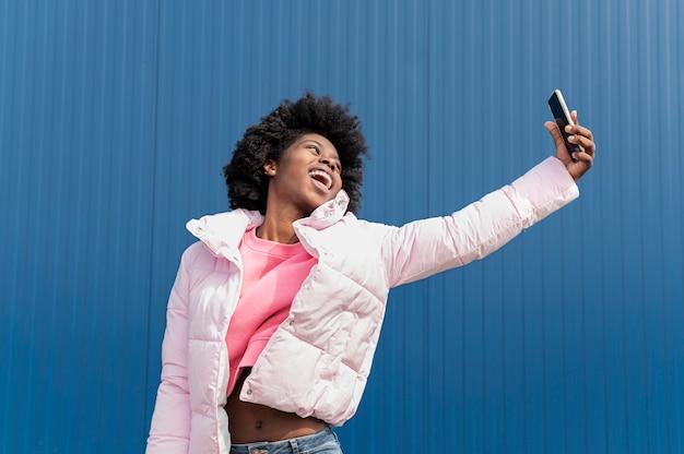 Portret jonge vrouw met mobiel springen