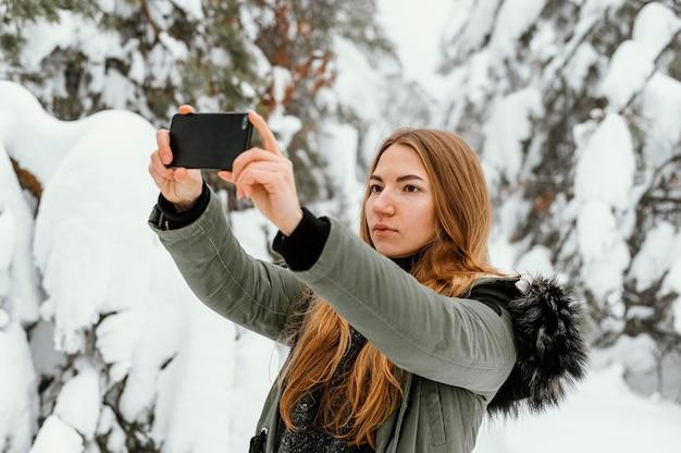 Portret jonge vrouw op winterdag foto nemen
