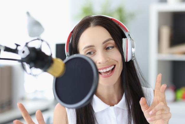 Portret jonge vrouw podcast opnemen in studio.