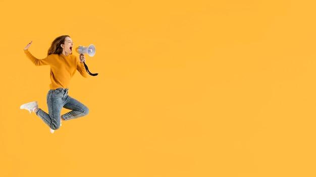 Portret jonge vrouw springen met megafoon