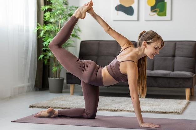 Portret jonge vrouw thuis oefenen op de mat