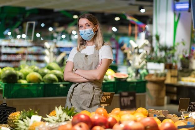 Portret jonge vrouw werknemer verkoper in een groente sectie supermarkt staande in een beschermd gezichtsmasker armen gekruist. groenteboer vrouw kijken camera in fruit winkel markt werknemer in een werkschort