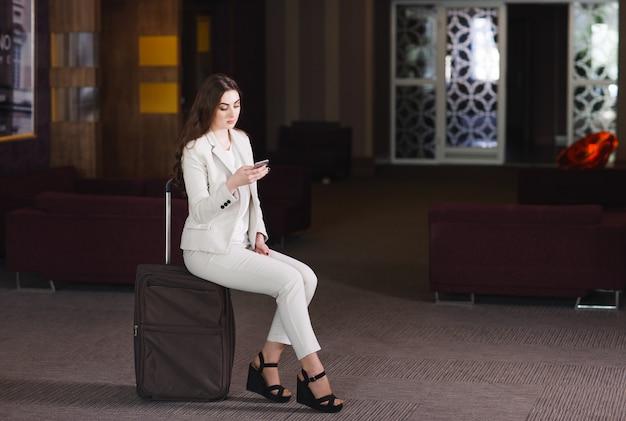Portret jonge vrouw zittend op koffers in de terminal of het treinstation, de vrouw ontmoette op een reis.