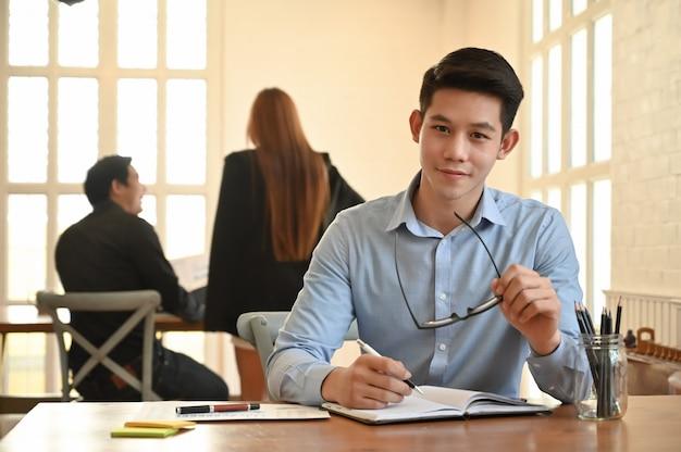 Portret jonge zakenman in naaiatelierruimte