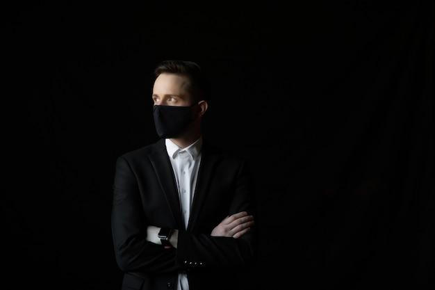 Portret jonge zakenman in pak met gekruiste armen dragen gezichtsmasker