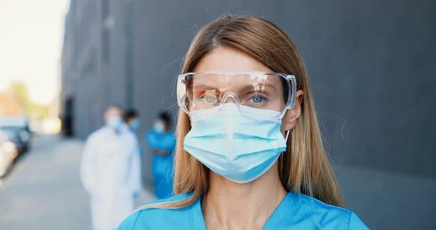 Portret kaukasische mooie vrouw arts in medische masker en bril camera kijken. vrouwelijke arts in ademhalingsbescherming close-up. multi-etnische artsen op achtergrond. inzoomen. dolly shot