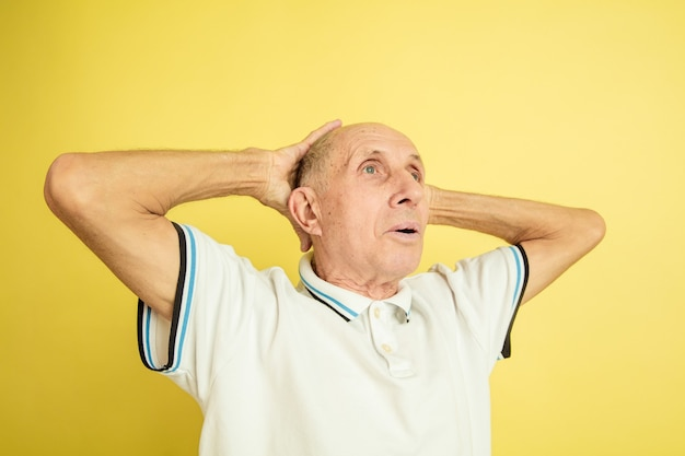 Portret kaukasische senior man geïsoleerd op geel
