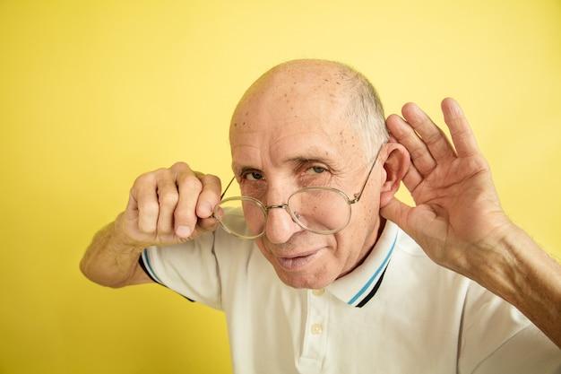 Portret kaukasische senior man geïsoleerd op gele studio