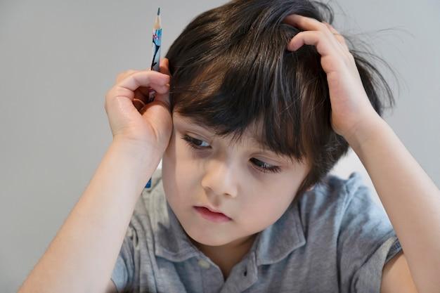 Portret kid jongen met zwarte pen alleen zitten en naar beneden te kijken met verveeld gezicht, eenzaam kind op zoek naar beneden aan tafel met droevig gezicht, vijf jaar oud kind verveeld met school huiswerk, verwend kind