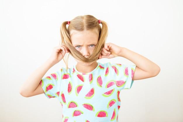 Portret kind meisje fronsende wenkbrauwen, bedekt haar gezicht met vlechtjes