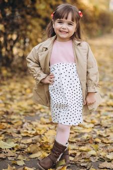 Portret klein meisje in een beige jas loopt in de herfst park