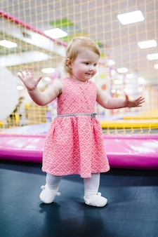 Portret kleine schattige baby kind meisje prinses baby 1-2 jaar spelen en springen op een trampoline in de speelkamer van de kinderen, binnen op verjaardagsfeestje. viering concept vakantie, evenement, entertainment.