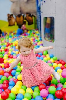 Portret kleine schattige babymeisje prinses baby 1-2 jaar staan en spelen met ballonnen, kleurrijke ballen in de speeltuin, ballenbak, droog zwembad voor verjaardagsfeestje. viering eerste jaar concept.